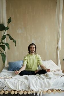 Uomo armonico nella posa del loto sul letto, persona rilassata in asana yoga e mudra che pratica la meditazione a casa sul letto
