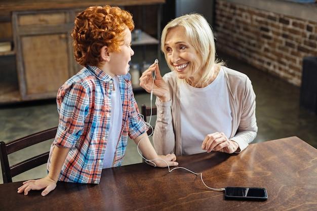Famiglia armoniosa. fuoco selettivo sulla signora senior allegra che sorride ampiamente mentre mette gli auricolari e ascolta il suo nipote dai capelli ricci che le parla.