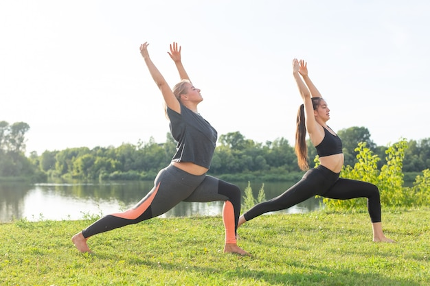 Armonia e concetto di stile di vita sano - giovani donne magre in abbigliamento sportivo che praticano yoga all'aperto.