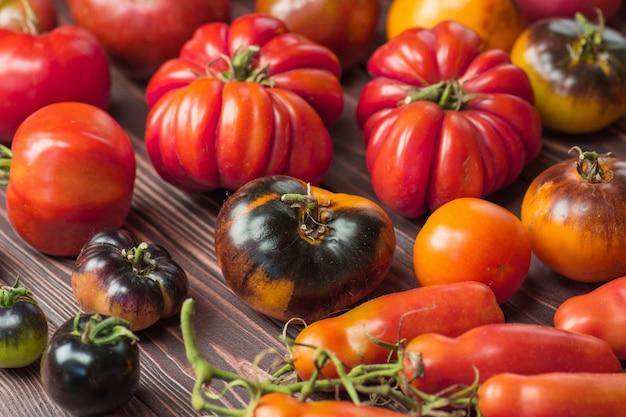 La raccolta dei pomodori assortiti. bei pomodori maturi di diverse varietà. sfondo di pomodori colorati o texture.