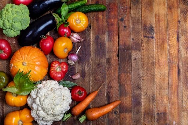 Raccolta delle verdure fresche dell'azienda agricola sulla vecchia tavola di legno d'annata stagionata rustica