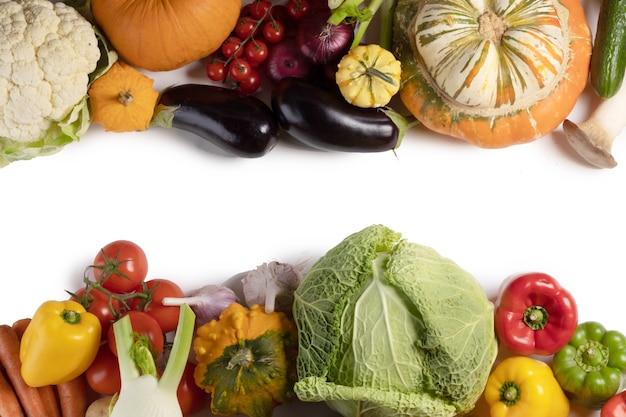 Raccolto di molte verdure isolato su sfondo bianco bordo cornice con copia spazio per il testo