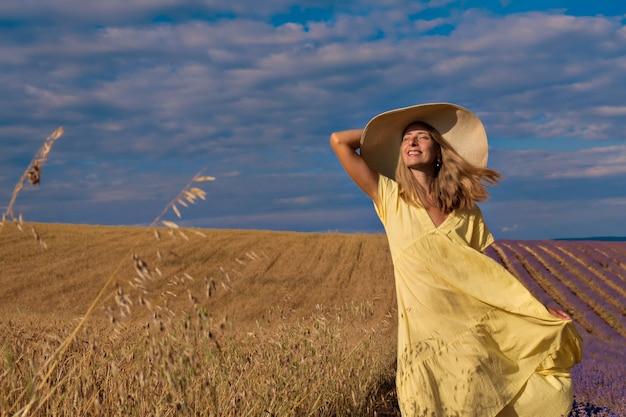 Il grano maturo del raccolto cresce nel campo il grano dorato e la ragazza sta camminando attraverso il campo...