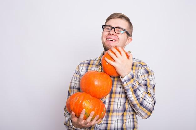 Raccolta di halloween e concetto di persone uomo con occhiali neri che tengono tre zucche su bianco