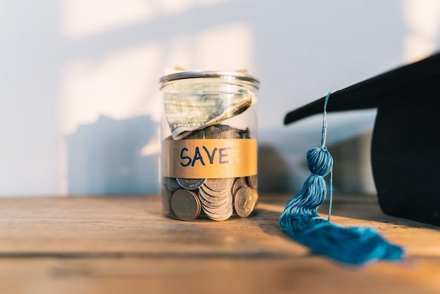 Cappello di laurea e monete di denaro per il risparmio