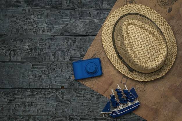 Un cappello, un modellino di nave e una macchina fotografica su un pezzo di carta vecchia su un tavolo di legno. il concetto di pianificazione del viaggio.