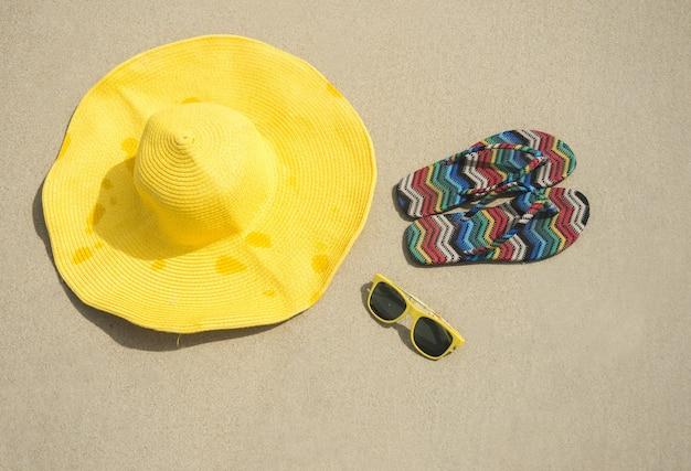 Cappello nella sabbia con occhiali da sole e scarpe da ginnastica