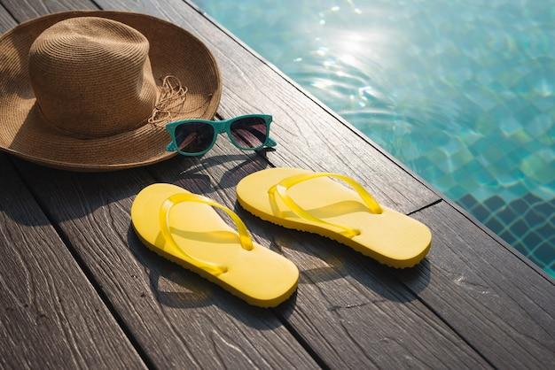 Cappello, occhiali da sole e infradito a bordo piscina