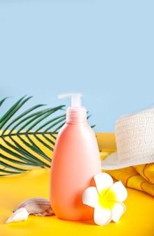 Cappello, tubetto di crema solare, fiore di plumeria frangipani, foglia di palma e conchiglie