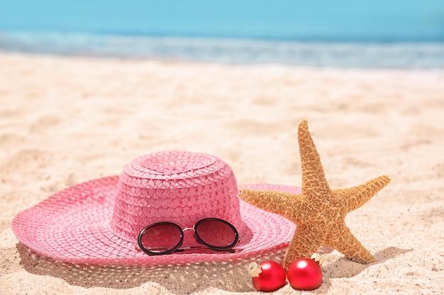 Cappello con stella marina, decorazioni e occhiali da sole sulla spiaggia. concetto di vacanze di natale