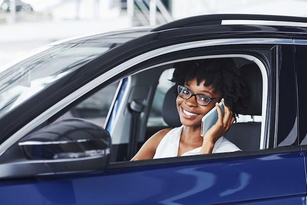 Parla al telefono. la giovane donna afroamericana si siede all'interno della nuova automobile moderna.