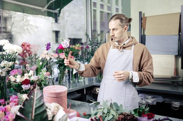 Dare un'occhiata. fiorista elegante bello che indossa il grembiule mentre si lavora nel negozio di fiori