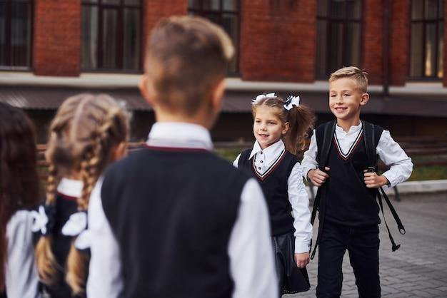 Avere un incontro. gruppo di ragazzi in uniforme scolastica che è insieme all'aperto vicino all'edificio scolastico.
