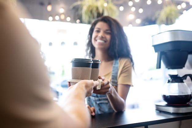 Buona giornata. gioiosa carina giovane donna mulatta prendendo il caffè da asporto dal barista di ottimo umore