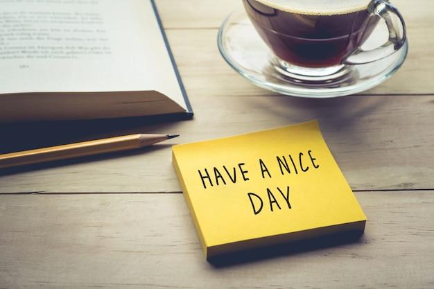 Buona giornata di testo con carta da lettere, blocco note e tazza di caffè sul tavolo della scrivania al mattino