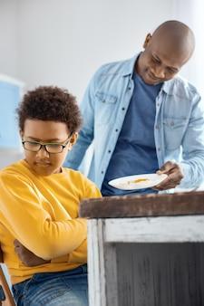 Mangia qualcosa. il giovane padre premuroso che dà un piatto con un uovo fritto al figlio, offrendolo da mangiare, mentre il ragazzo gira la faccia dall'altra parte