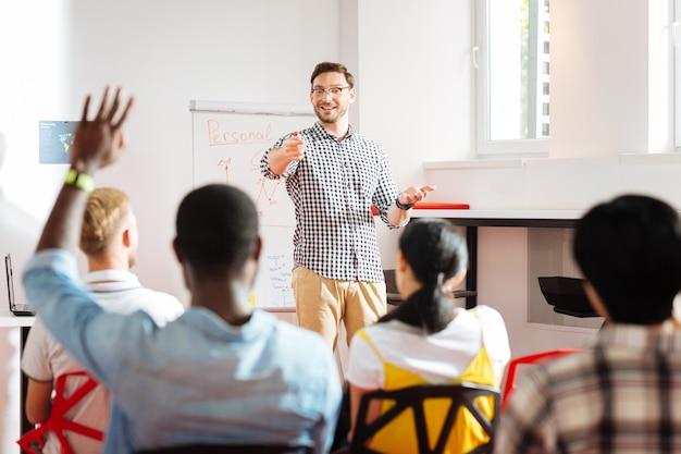 Avere risposte. sorridente imprenditore emotivo che conduce un seminario e uno studente alzando la mano pur avendo domande