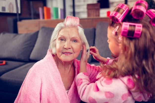Avere il giorno della bellezza. bella signora anziana che si sente bene con la giornata della bellezza con la sua graziosa nipotina premurosa