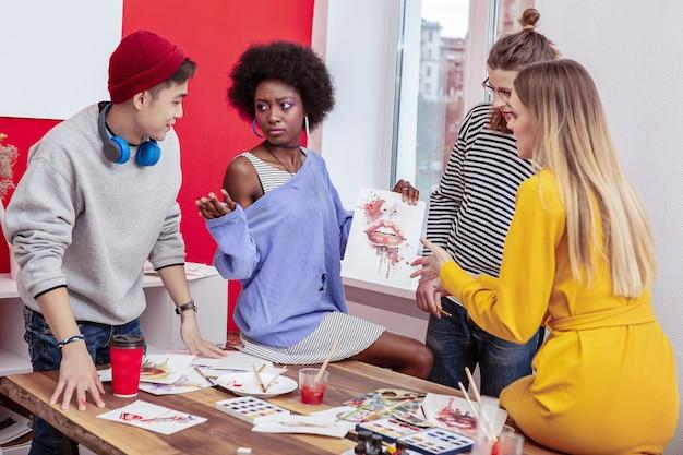 Discussioni. quattro studenti attivi intelligenti che discutono sulla pittura creativa