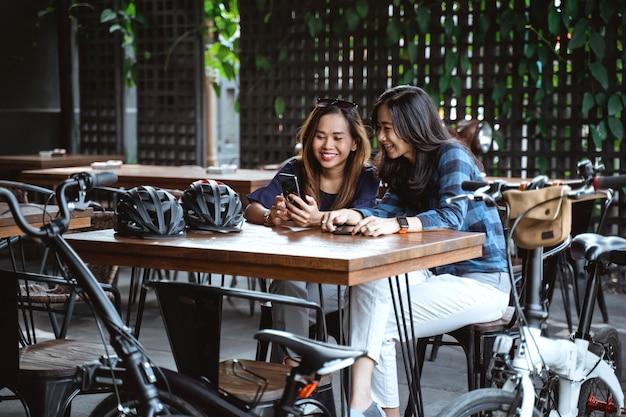 Divertendosi donna asiatica che gode della chiacchierata e che per mezzo dello smartphone quando una pausa al caffè
