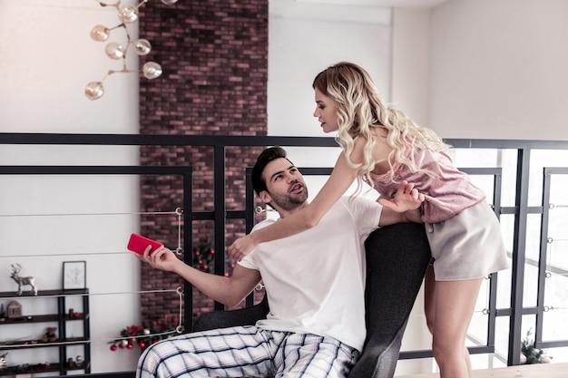 Divertirsi. giovane barbuto dai capelli scuri che indossa una maglietta bianca divertendosi con sua moglie