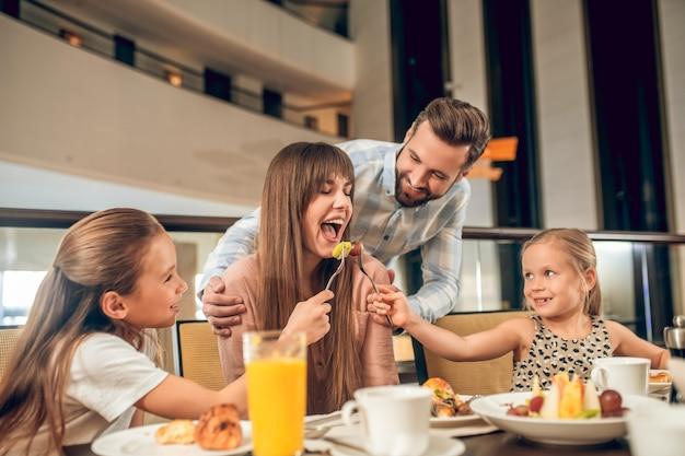 Divertirsi. famiglia sorridente che si siede al tavolo e si diverte