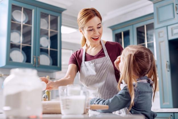 Divertirsi insieme. felice giovane donna asciugando la farina dalla fronte delle figlie e ridendo in modo divertente mentre cuociono i biscotti insieme a lei