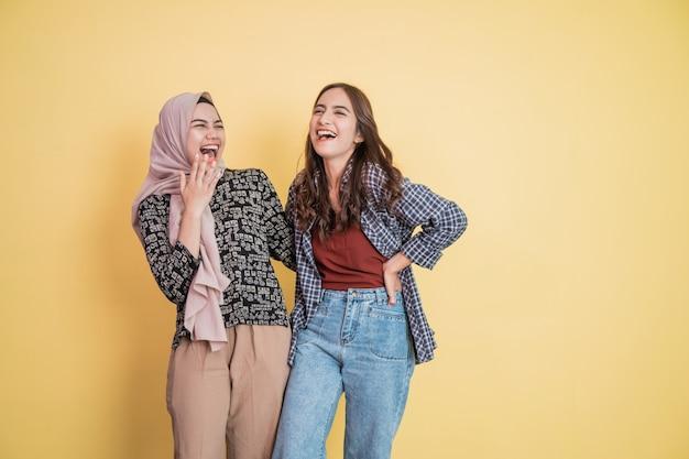 Divertirsi con due belle donne che ridono mentre chiacchierano e si abbracciano con le mani sulle spalle con...