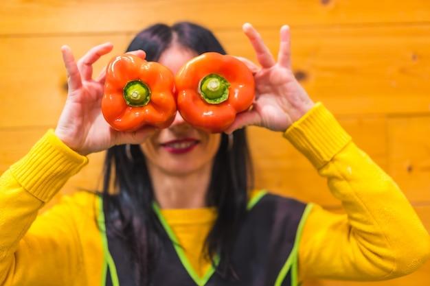 Divertirsi con i peperoni rossi in mano a una ragazza bruna caucasica che lavora in un fruttivendolo