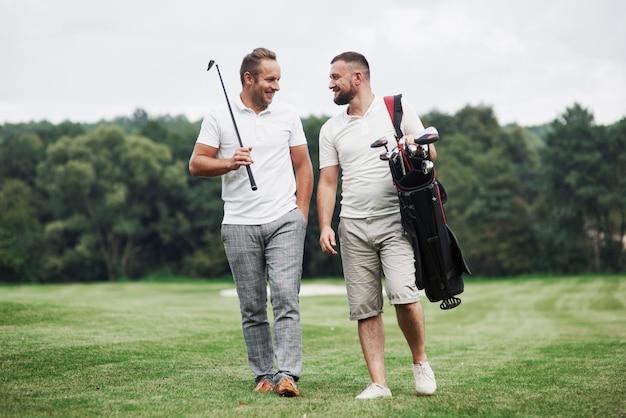 Divertirsi. due amici che camminano nel prato con attrezzatura da golf e parlano.