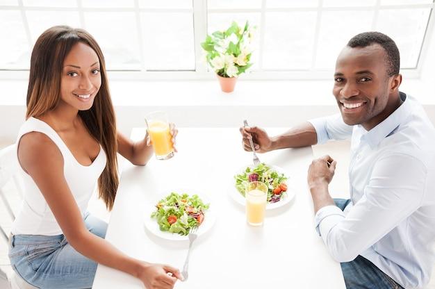 Fare una sana colazione. vista dall'alto di una bella giovane coppia africana seduta insieme a tavola e mangiare insalate con succo d'arancia