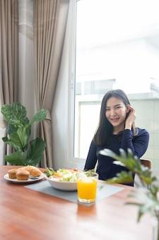 Avendo il concetto di pasto una bella donna che mescola zero calorie condimento per insalata con un'insalata verde nella ciotola.