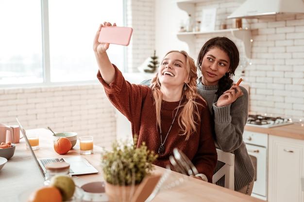 Avendo incontro. belle ragazze dai capelli lunghi che fanno selfie insieme in cucina mentre mangiano spuntini sani