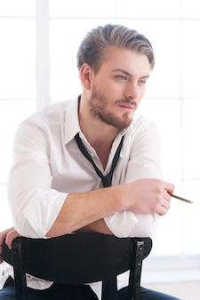 Avere una pausa per fumare. giovane premuroso in camicia e cravatta che fuma una sigaretta e guarda lontano mentre è seduto sulla sedia