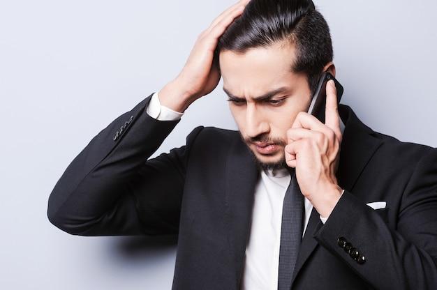 Avere qualche problema. giovane uomo d'affari frustrato che parla al telefono cellulare e si tocca la testa mentre si trova in piedi su uno sfondo grigio