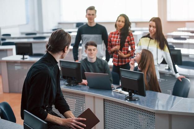 Avere un discorso. gruppo di giovani in abiti casual che lavorano nell'ufficio moderno.