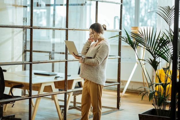 Avere videochat. donna d'affari incinta che indossa un maglione beige con chat video sul laptop