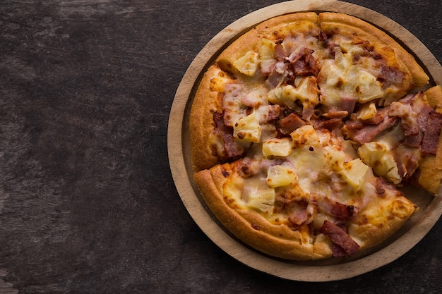 Pizza hawaiana di sapore sul piatto di legno con fondo di legno nero scuro. concetto di fast food.