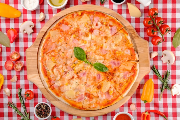 Pizza italiana hawaiana con parmigiano, ananas, mais, condimenti di prosciutto, basilico fresco e salsa di pomodoro su una tavola di legno