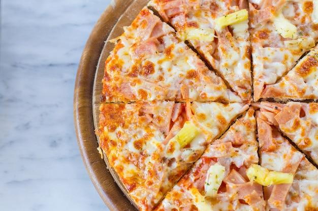 La pizza hawaiana è un alimento italiano fatto con salsa di pomodoro, ananas tritato, prosciutto e formaggio.