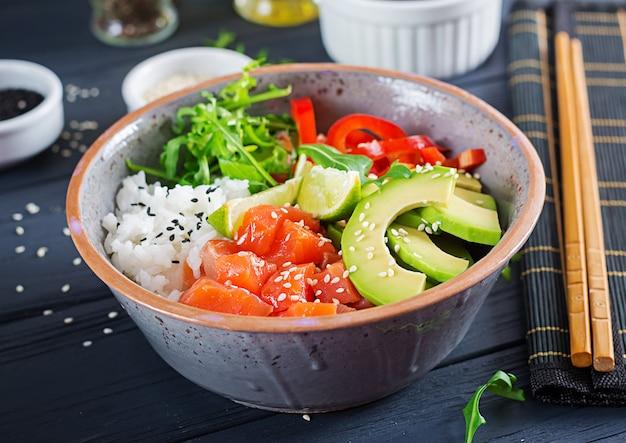 Ciotola di poke di pesce salmone hawaiano con riso, avocado, paprika, semi di sesamo e lime. ciotola di buddha. dieta alimentare.