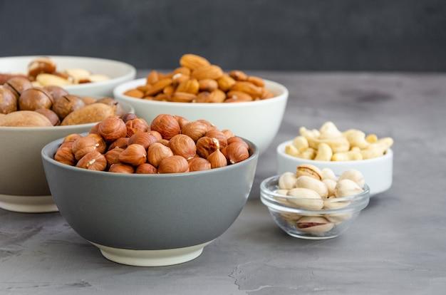 Nocciole, mandorle, noci brasiliane, anacardi, macadamia, noci pecan e pistacchi in ciotole su uno sfondo di cemento scuro. cibo salutare.
