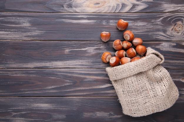 Nocciole nel sacco sulla tavola di legno marrone