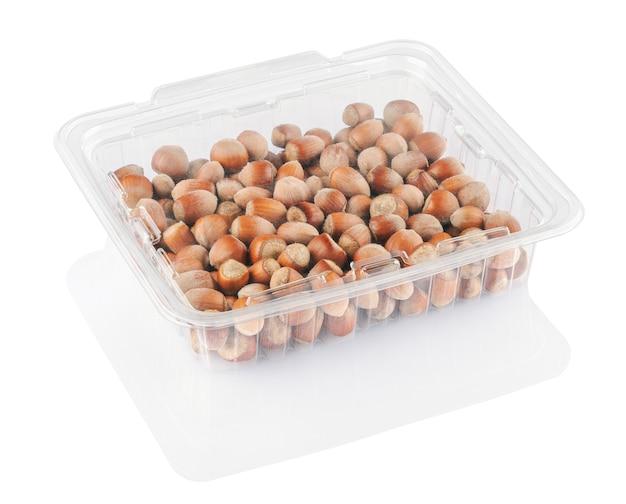 Nocciole in contenitore trasparente isolato