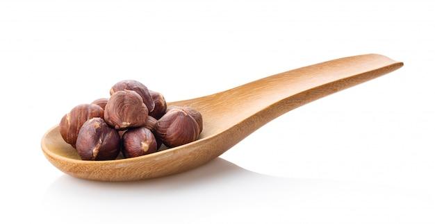 Nocciole in cucchiaio di legno su bianco