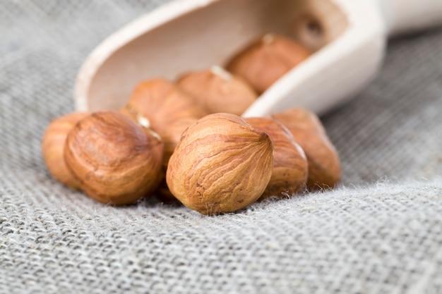 Nocciole in un cucchiaio di legno gran numero di nocciole sbucciate durante la cottura il primo piano della pianta viene utilizzato nel cibo delle persone