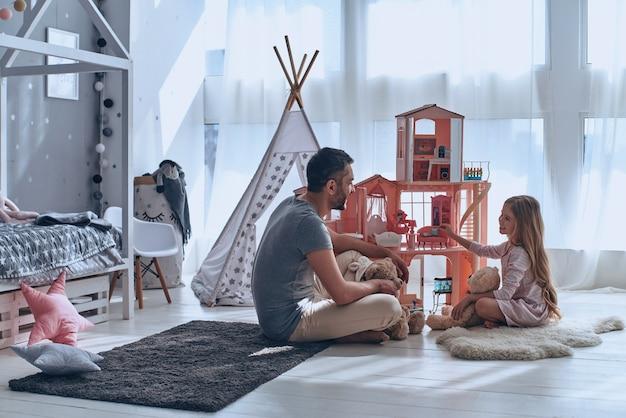 Lui la capisce sempre. padre e figlia giocano insieme con una casa delle bambole seduti sul pavimento in camera da letto