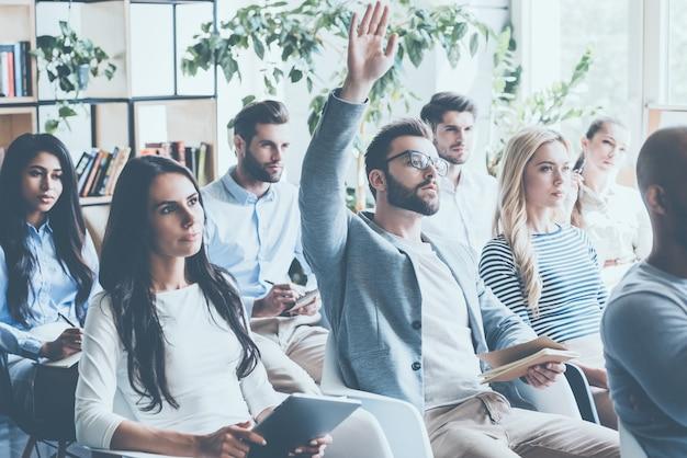 Ha alcune domande. gruppo di giovani seduti in conferenza insieme mentre un uomo alza la mano