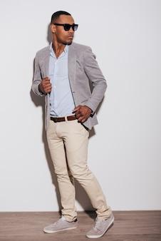 Ha un look alla moda. fiducioso giovane africano in abbigliamento casual intelligente guardando sopra la spalla