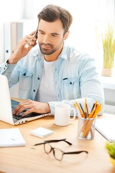 È sempre al lavoro. bel giovane in camicia che parla al telefono e lavora al computer portatile mentre è seduto al suo posto di lavoro